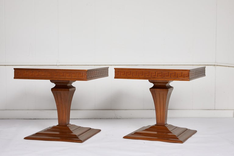 Midcentury pair of low square side or end tables with a checkered veneer top and Greek key apron over a carved urn shaped pedestal and tiered platform base. The vintage tables are symmetrical and finished on all sides.