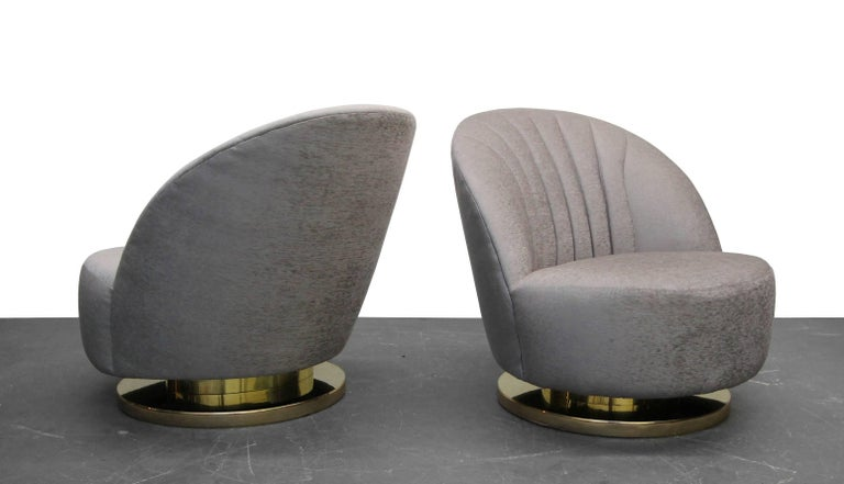 Beautiful pair of midcentury swivel slipper chairs with brass bases by Milo Baughman. A truly gorgeous pair of slipper chairs.   Chairs have been professionally reupholstered with all new foam and beautiful pale lilac velvet.