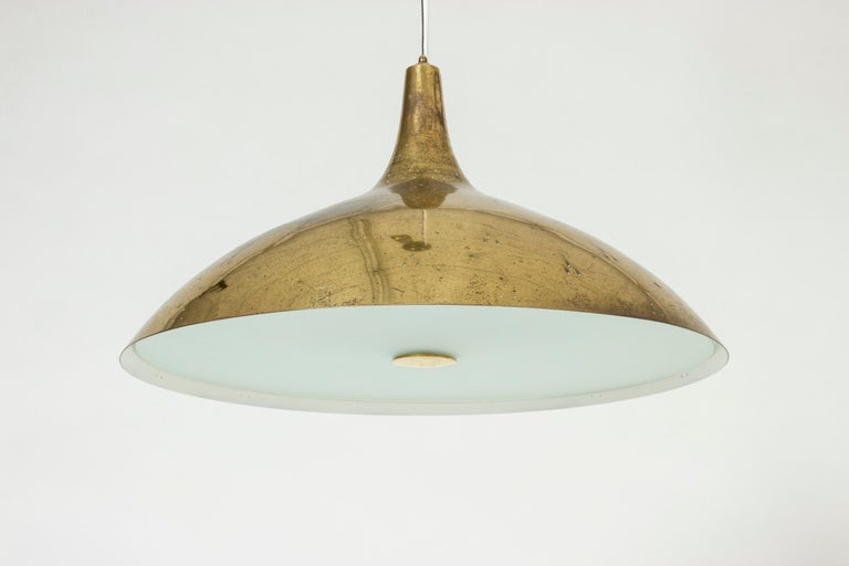 Elegant brass ceiling lamp by Paavo Tynell, with a streamlined shade perforated with small holes. The underside of the lamp has a glass shade that covers the light source. Suspended with a brass cord, height adjustable with a brass