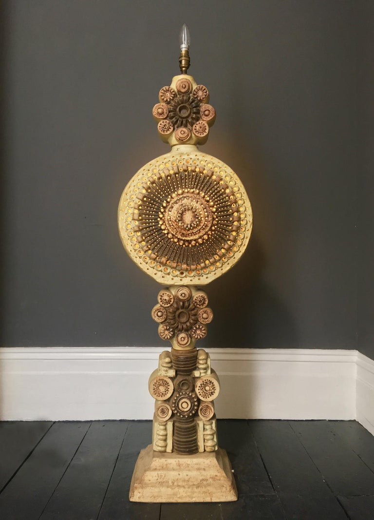 A monumental ceramic TOTEM floor lamp with pierced detail by Bernard Rooke, England, 1970s.  An impressive sculptural piece, made up of cast ceramic elements in natural tones, on a metal tube. The ceramic includes a large central section which is