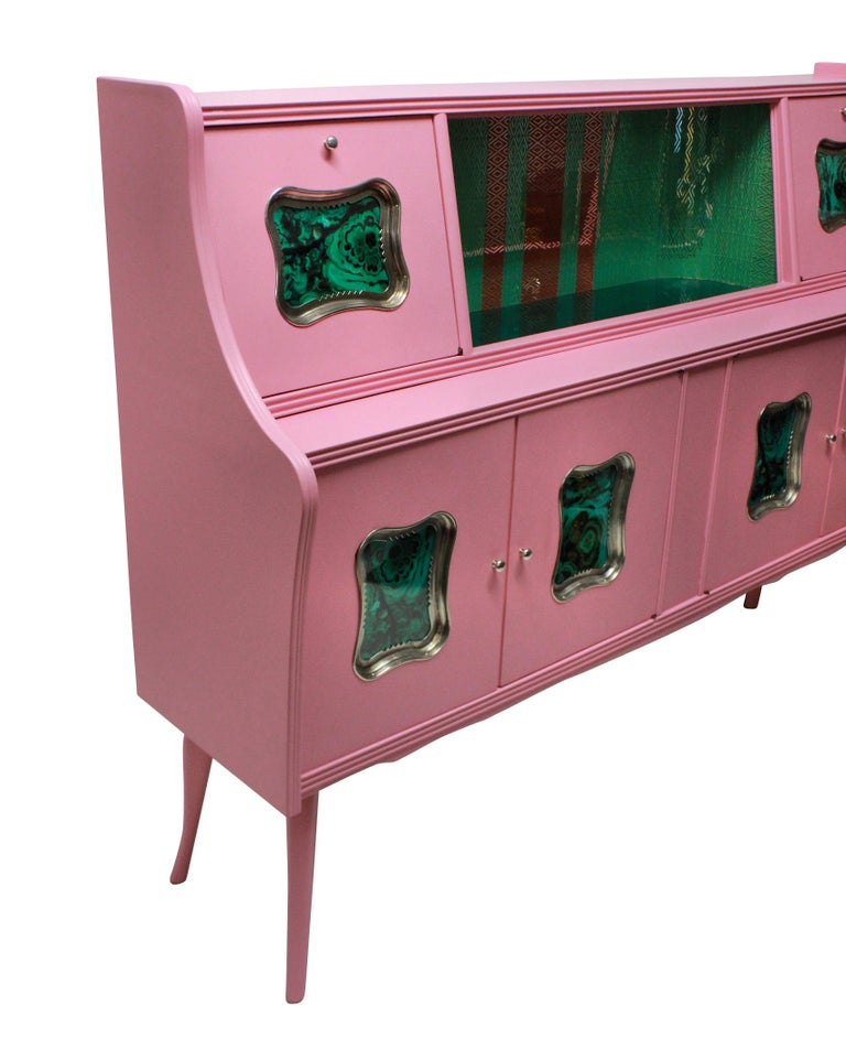 An Italian bar cabinet in pink lacquer with a central green glass mosaic section, two drop down doors either side and cupboards beneath. With faux malachite panels in silver plated frames.