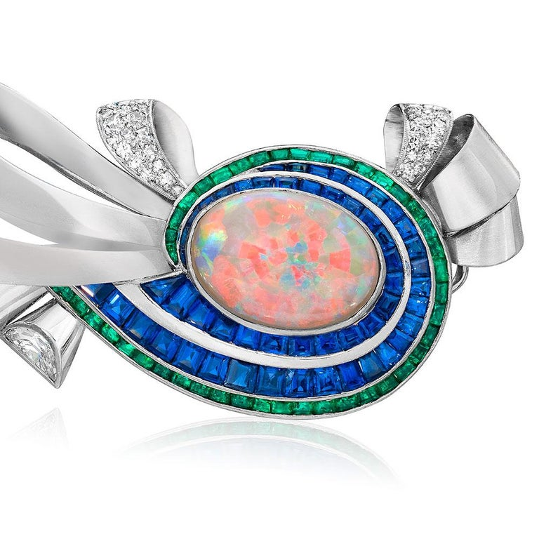 A swirling array of gemstones are set in this elegant mid century brooch. The center features a 5.73 carat oval Opal. Two rows of graduating calibre cut Blue Sapphires weighing 6.75 carats, and one row of calibre cut Emeralds weighing 2.31 carats