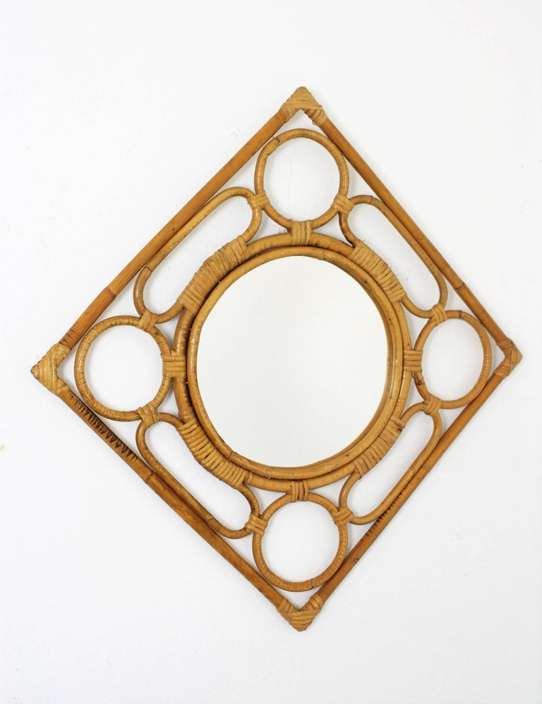 A lovely handcrafted bamboo and rattan mirror with squared /rhombus shape and a highly decorative frame with ovals and circles. Spain, 1960s. It has all the taste of the Mediterranean coast. It can be hung as a rhombus or as a