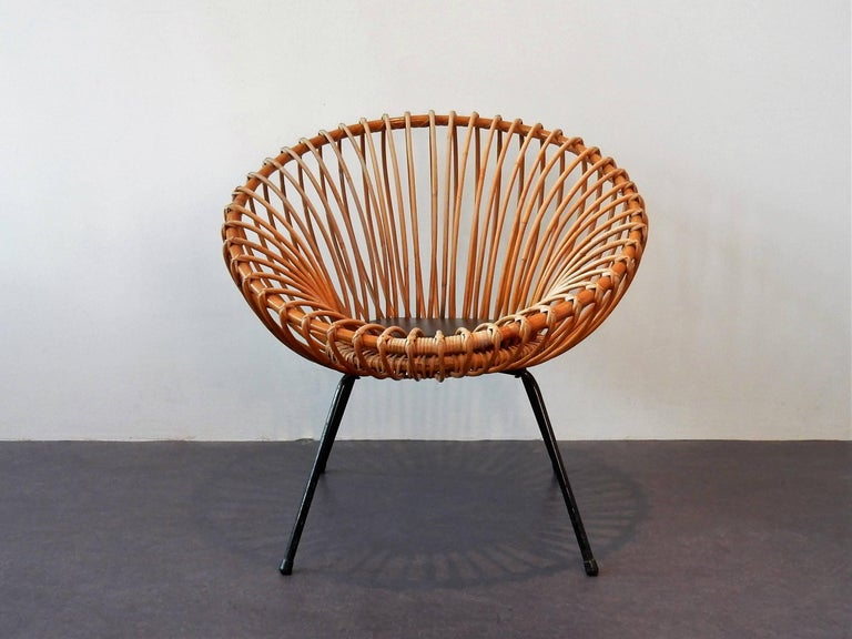 This is a very nice rattan scoop chair with a metal frame and a black faux leather circular seat pad. The chair is in the style of Rohé and Italian designer Franco Albini. It is in a very good condition considering age and use. Some signs of age and