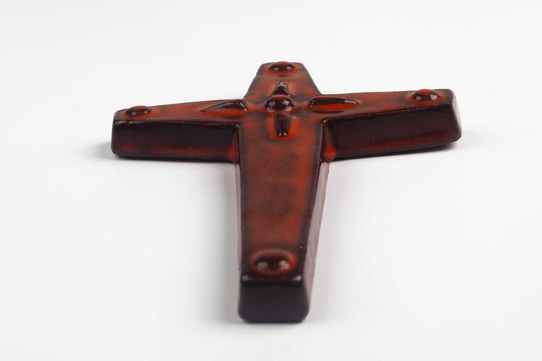 Midcentury European wall cross in glazed, hand painted ceramic with decorative volume. From a large collection of vintage crosses handmade by Flemish artisans.   From modernism to brutalism, the crosses in our collection range from being as