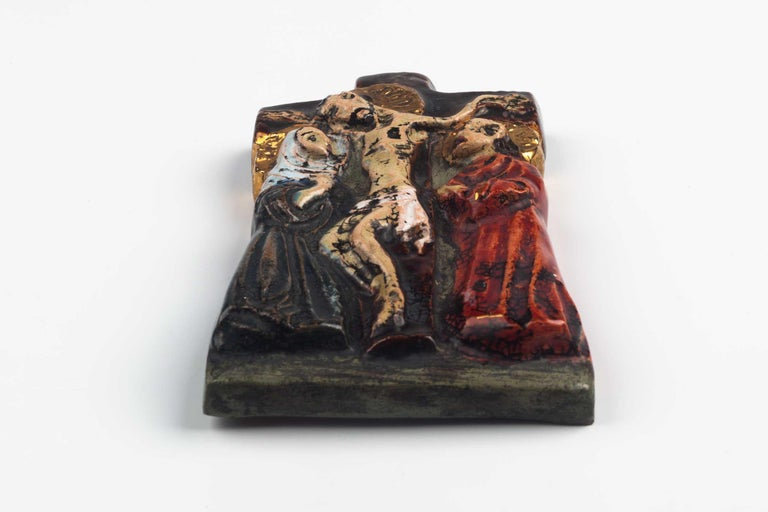 Midcentury European wall crucifix in glazed, hand painted ceramic depicting scene of Christ at the cross surrounded by Mary, mother of Jesus and Mary Magdalene. From a large collection of vintage crosses handmade by Flemish artisans.   From