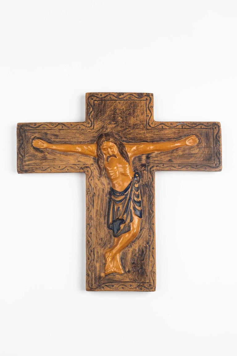 Midcentury European wall crucifix in glazed, hand painted ceramic. From a large collection of vintage crosses handmade by Flemish artisans.   From modernism to brutalism, the crosses in our collection range from being as futurist as a modernist