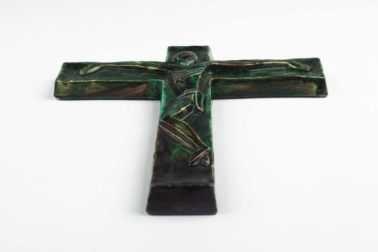 Midcentury European wall crucifix in glazed, hand painted green ceramic depicting stylistic Christ on green cross. From a large collection of vintage crosses handmade by Flemish artisans.   From modernism to brutalism, the crosses in our