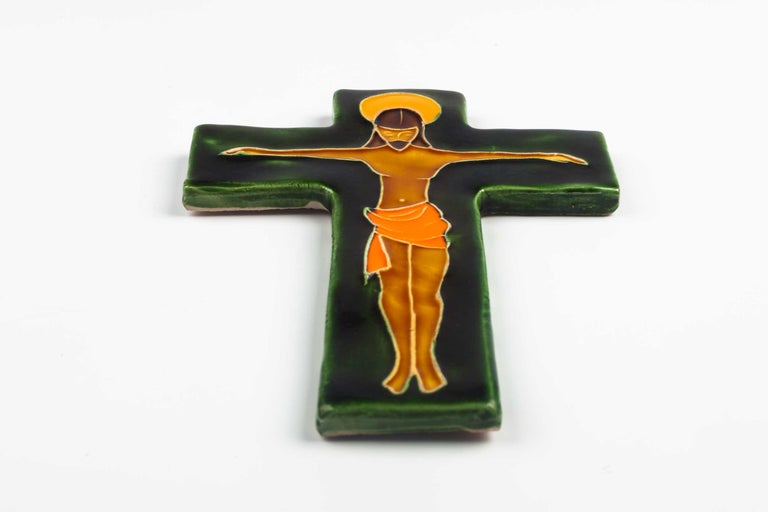 Midcentury European wall crucifix in glazed ceramic depicting stylistic Christ on green cross. From a large collection of vintage crosses handmade by Flemish artisans.   From modernism to brutalism, the crosses in our collection range from being