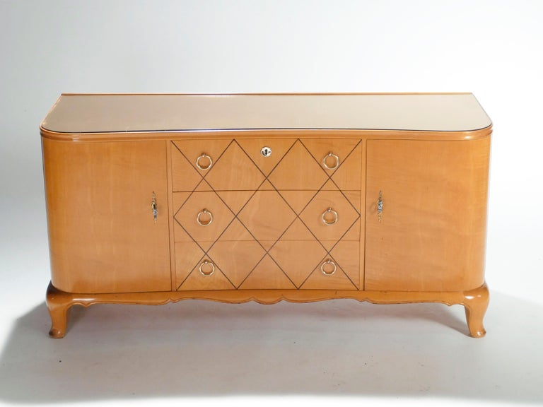Most likely originally intended for a bedroom, this 1940s chest of drawers or sideboard imparts a cosy, glowing mood to a space. The warm sycamore maple remains looking healthy and smooth eighty years later. Quality bronze rings and accents adorn