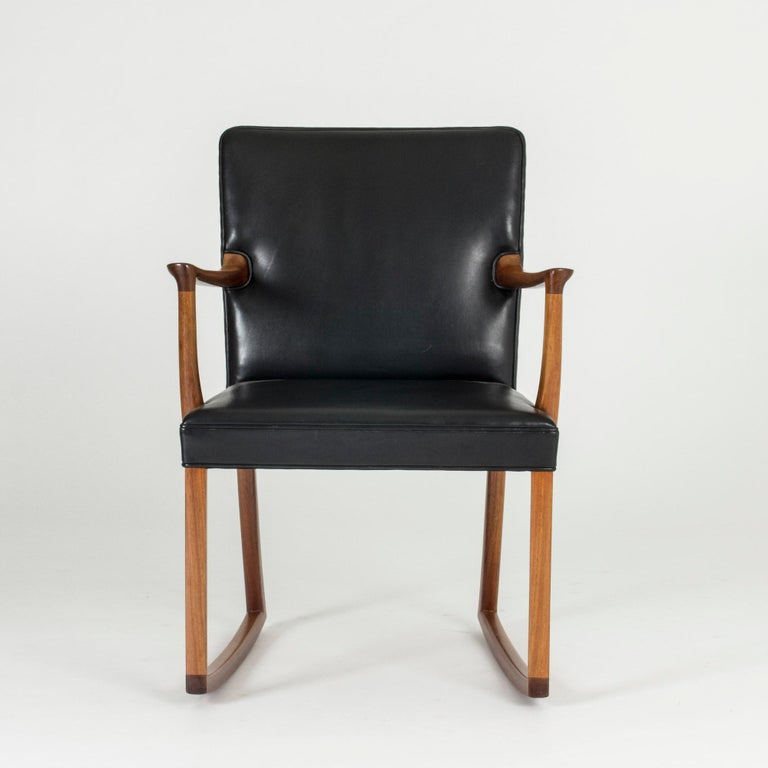 Awesome modernist rocking chair by Ole Wanscher, made with a rosewood frame and black leather seat and back. Great Silhouette. Sits perfectly behind a desk.