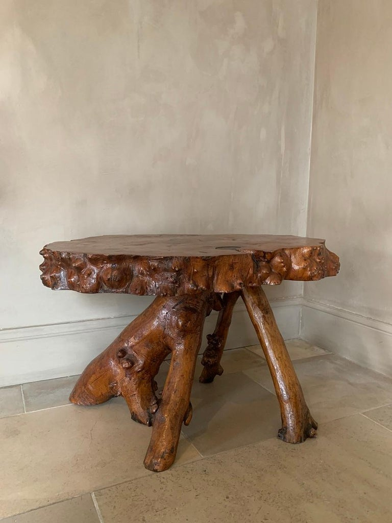 A great looking low root table. The organic feet in harmony with the natural top in one piece and with attractive small knots. No doubt this piece was made from the same tree by a skilled artisan.