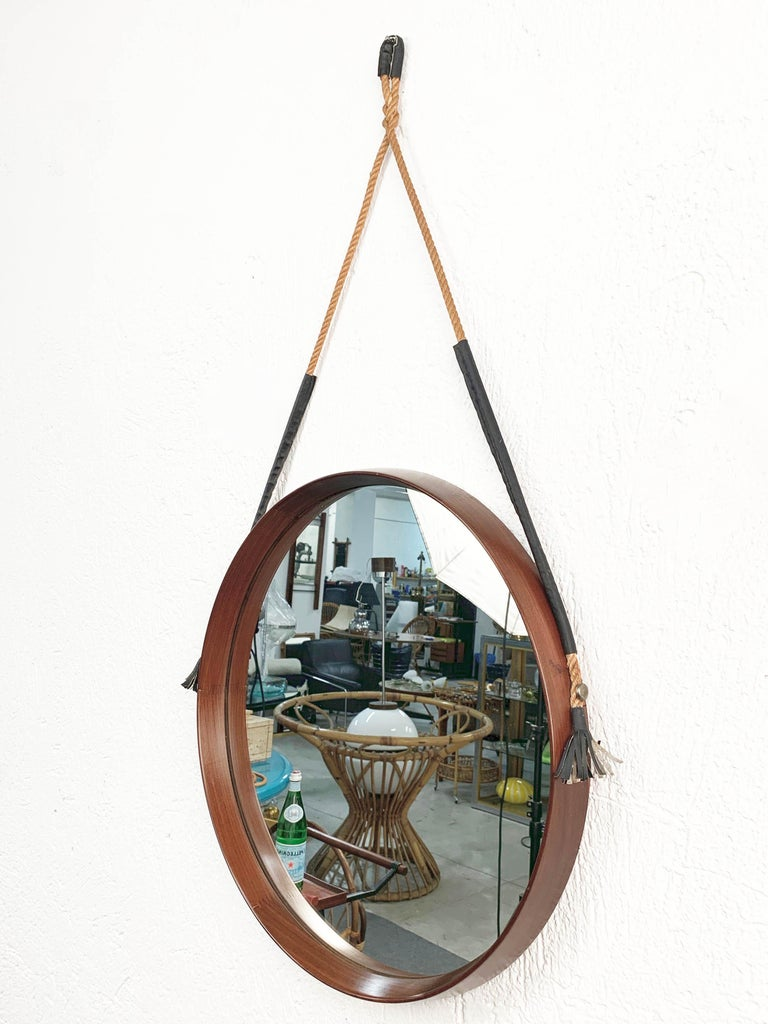 Vintage 1960s midcentury Italian round mirror with teak structure.  It can be hanged via a braided and black leather rope.  A fantastic item that will enrich a living room with its design and patina.