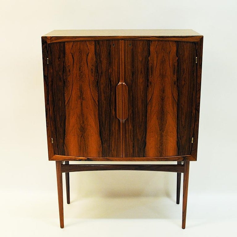 A beautiful vintage bar cabinet 'Baccus' by Torbjørn Afdal for Bruksbo A/S designed in 1955 and produced at Mellemstrands Møbelfabrikk AS. Norway. The cabinet is made of rosewood and black formica. Furnished with a handy pull-out preparation