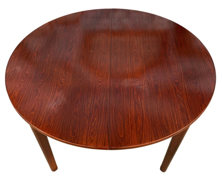 Midcentury rosewood expandable round dining table with 1 nesting leaf. This is a beautiful dining table Made in Denmark. Amazing solid wood legs. Made, circa 1960. Original finish in excellent condition. Documented AM Mobler. Measures: 48
