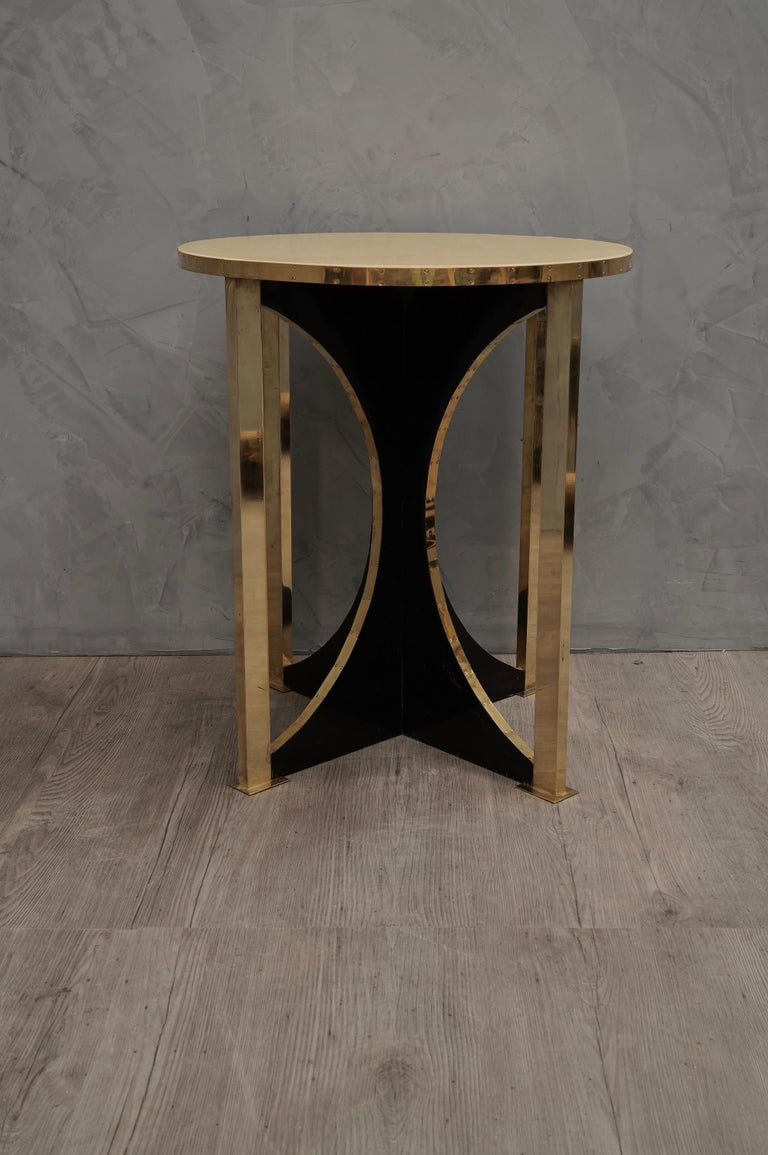 Fine and refined materials for a pair of very elegant side tables, shortly after the middle of the last century.  Top in circular shape completely covered in parchment leather, polished in resin. Below, particular the shape of the leg, wooden