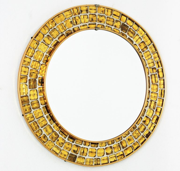 Spanish midcentury mosaic round mirror framed with golden textured glass tiles. Spain, 1960s. This gorgeous Mid-Century Modern mirror features a tile mosaic with small pieces of textured irisdiscent glass in gold color cased on a white background