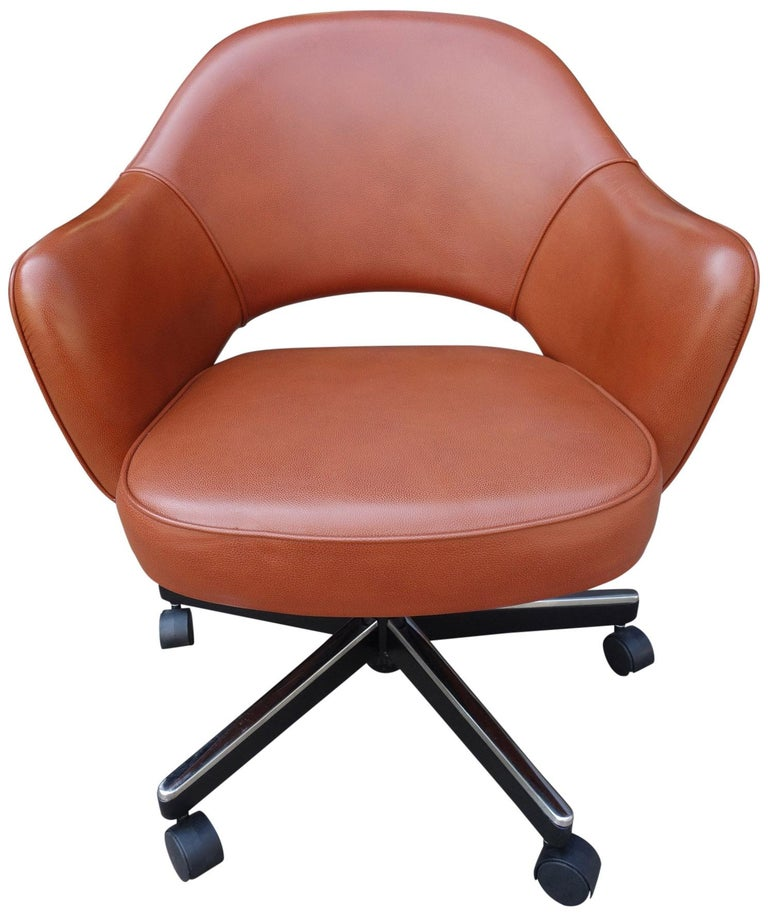 Midcentury Saarinen Executive chairs in reddish brown leather. All with adjustable pneumatic height and tilt positions. This iconic design has been a favorite in both the home and corporate settings due to its sharp looks and comfort. Seat height