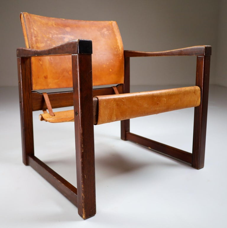 Safari lounge chair in absolutely gorgeous patinated cognac saddle leather and solid pinewood, circa 1970s. The thick saddle leather is beautifully patinated during use and age and shows interesting stitching. European pine wood with thick saddle
