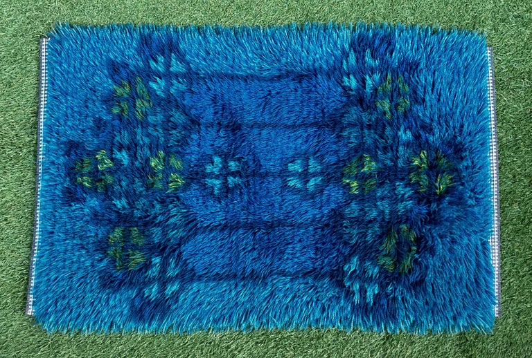 A silky midcentury high pile Scandinavian rya rug or wall hanging dating, circa 1960s. The vintage rug was crafted from hand knotted wool in several shades of blue with yellow and green accents creating a pattern with strong secessionist and Celtic