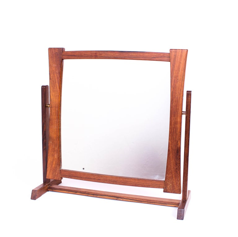 A midcentury table mirror by unknown Scandinavian designer. The mirror is made out of rosewood with brass fittings. Very good vintage condition, one small dark spot on mirror.