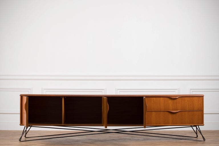 Midcentury teak sideboard from the 1960s. It is a shining example of the form and function synonymous with furniture of this era. It has is all, well-built, great design and heaviness. Two large drawers and three doors hiding storage space. The most