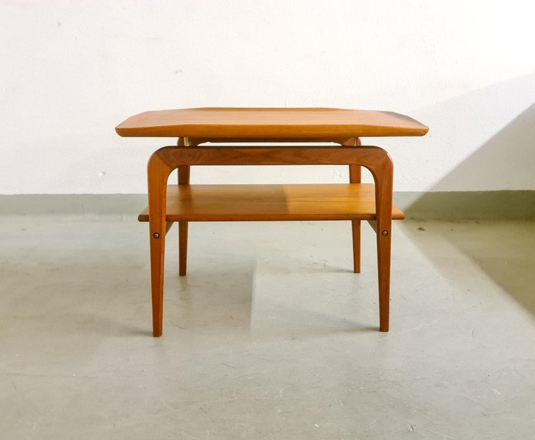 A Classic Danish side or occasional table by Arne Hovmand-Olsen for Mogens Kold. Teak wood with teak shelf and raised edges-quality construction. Solid, elegant and practical with beautiful patina and excellent condition.  Good vintage condition