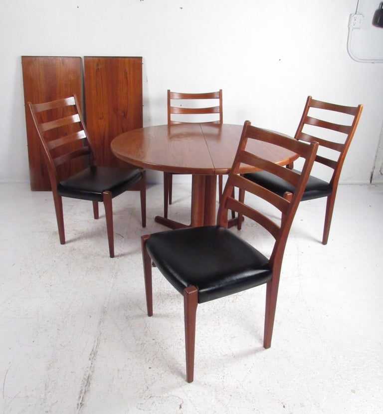 A stunning vintage modern Danish teak pedestal base dining table with two leaves by Skovby Mobelfabrik. This attractive set caters to many with the ability to expand from 46.5 inches to 85 inches wide. The sleek set of four dining chairs boast teak