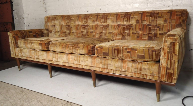 Long sofa with walnut legs and trim by John Widdicomb. Attractive brass foot caps and tufted back.  (Please confirm item location NY or NJ with dealer).