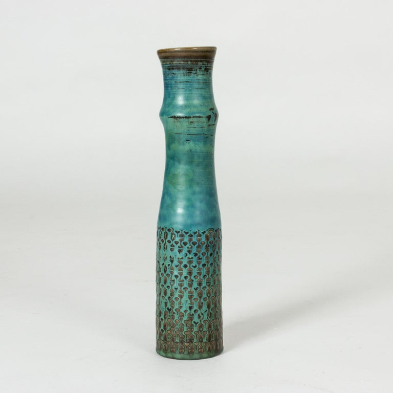 Unique stoneware vase by Stig Lindberg. Slender, elongated shape with a graphic pattern characteristic of Lindberg and beautiful shades of blue, brown and green.