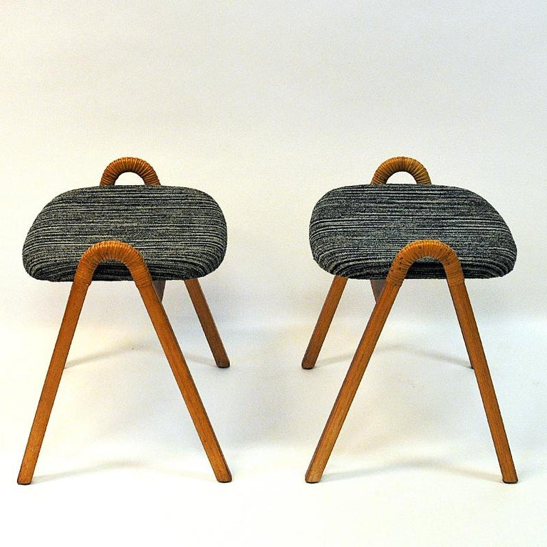 Lovely pair of vintage stools with original seat fabric and rattan handles produced by Møre Lenestolfabrikk, 1950s, Norway. Original black/beige striped cushions and lovely sculped side handles. Great pair of stools perfect as extra chairs or