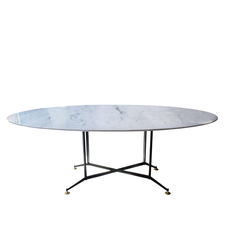 Dining table made up of black lacquered iron structure, with height adjustable brass finished legs; and oval Carrara marble top.