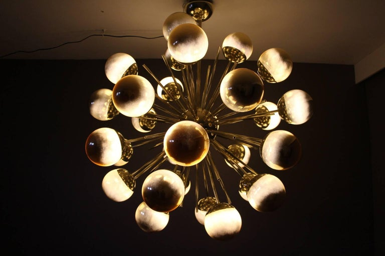This very chic chandelier features brass rods ending with gold glass globes.