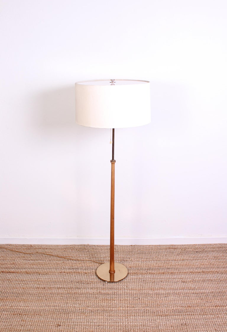 A midcentury floor lamp of high quality by Swedish manufacturer Bergboms. The lamp is made out of brass and teak with its original shade. Good vintage condition with signs of usage consistent with age.