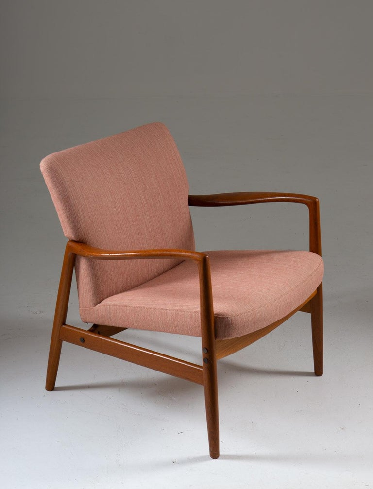 Rare Mid-Century Modern lounge chair by Bertil Fridhagen for Bodafors (Sweden). This chair has a timeless classic design. It features a teak frame, holding the seating and backrest which are upholstered in a pink wool fabric. The armrests are