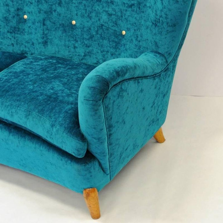 A rare and special one of a kind 1940`s sofa with high comfortable back and soft deep cushions that are removable. New upholstery in blue/green soft plush. Beautiful brass knobs decorations on the back. Wooden legs and stom. Swedish produced sofa of