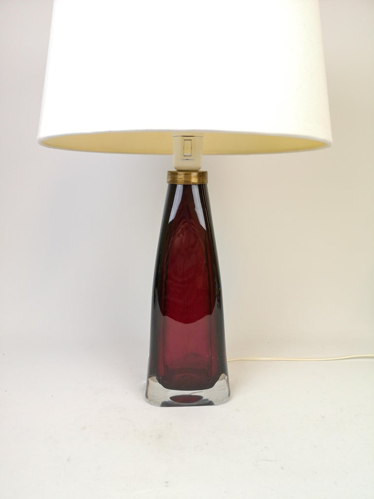 Table lamp in crystal, model RD1323 by Carl Fagerlund for Orrefors, Sweden. The lamps have a stunning red color with brass details.  The shade are not included.  Measures: H 39 cm.