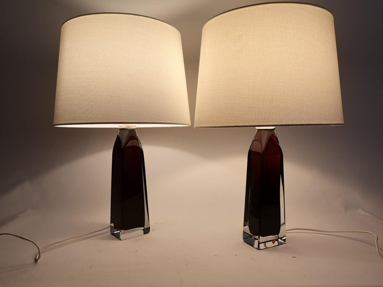 Table lamps in crystal, model RD1884 by Carl Fagerlund for Orrefors, Sweden. The lamps have a stunning red color with clear glass, and chrome details.  The shade can be included if buyer wants.  Measures: H 37 cm, W 8 cm, with shade H 52 cm.
