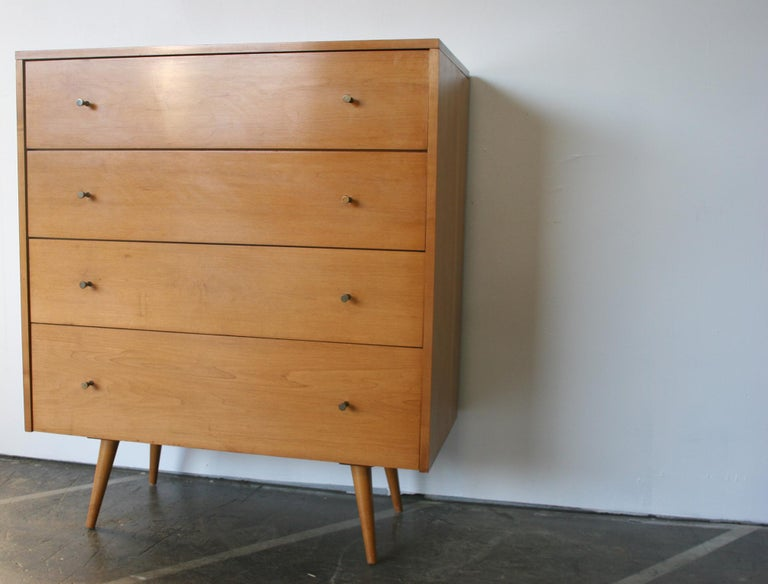 Beautiful midcentury tall dresser 4-drawer dresser by Paul McCobb circa 1950 Planner Group #1501 with 4 center drawers. Solid maple construction has a Beautiful Blonde Lacquered finish. All original Brass Cone pulls sits on 4 Solid Maple Tapered