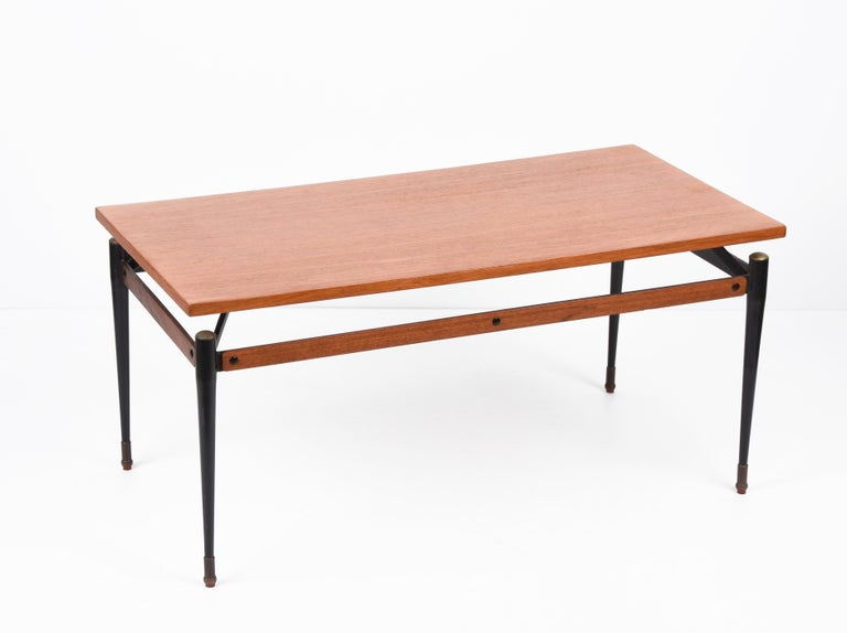 Spectacular coffee table in teak attributable to Silvio Cavatorta made of black enamelled iron and brass structure with red plastic feet. This wonderful piece was produced in Italy during the 1960s.  Everything in this article is very elegant: the