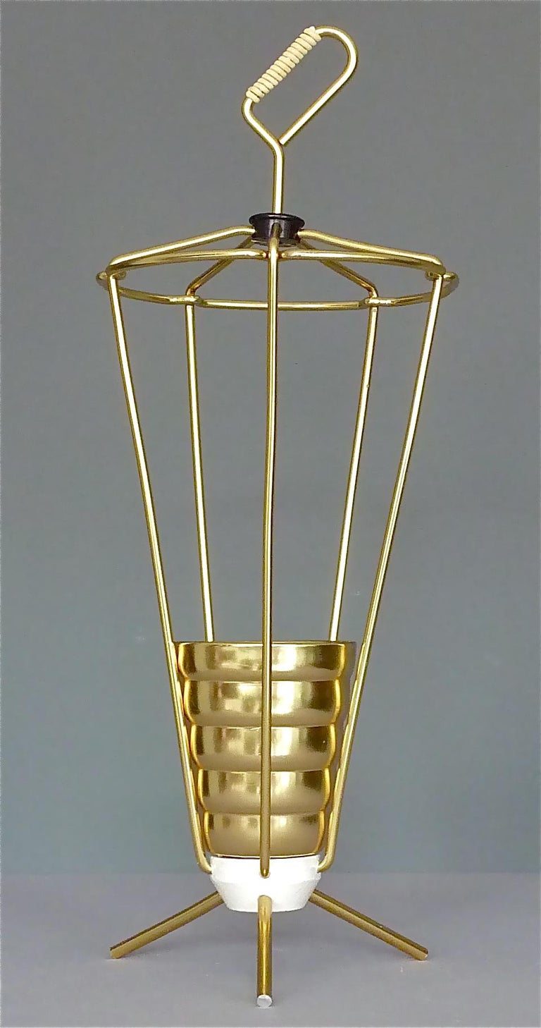 Nice Italian 1950s golden tripod umbrella stand. Golden anodized aluminum umbrella stand with white enameled iron weighted sputnik base, a golden beaker as raindrop-catcher and white plastic cord wrapping around the handle. Very good condition with