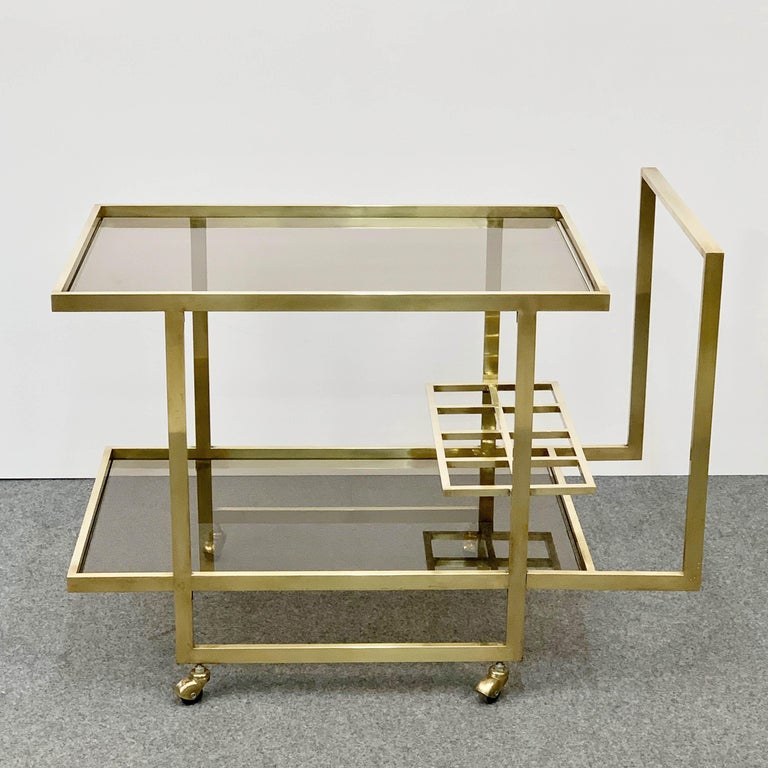 Exceptional two-level service midcentury brass cart produced in Italy during 1970, with bottle holder.  The brass is gold-plated and the glass is lightly smoked, with a perpendicular design the represents Italy during the 1970s at its best.  A