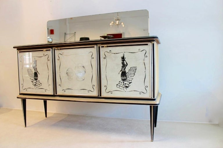 Rare and highly collectible bar credenza designed in Italy by Umberto Mascagni from Bologna. Early 1950s three doors cabinet created with reverse painted glass door fronts, two doors featuring a woman walking down the stairs, the central door