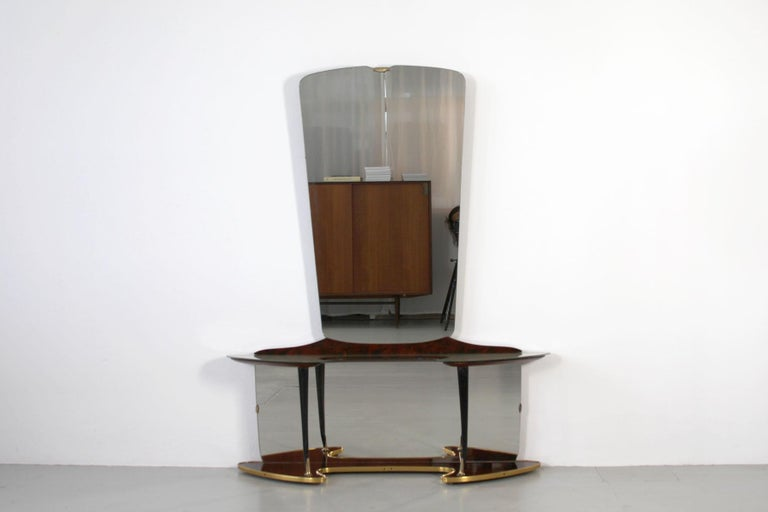 The vanity features a tapered vertical rectangular mirror on the top and a horizontal rectangular mirror in the bottom part of the piece. The console is shaped in an open curve which is also mirrored in shape by the bottom of the base. Additionally