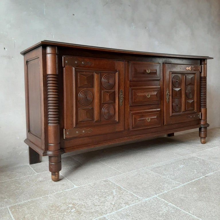 Midcentury vintage oak sideboard, credenza by Charles Dudouyt. This beautiful cabinet in Art Deco style shows off very fine craftsmanship. It features three drawers and two doors, decorated with typical Dudouyt geometrical shapes. This sideboard has