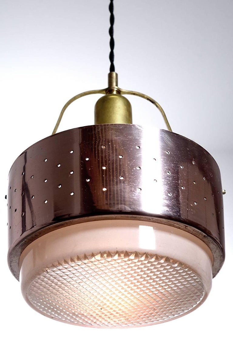 We have a collection of these unique simple Mid-Century Modern lamps. It consists of a perforated copper ring with a thick waffle pattern glass lens. It hangs from a brass bow and center socket. There is a nice open look to the whole design and they
