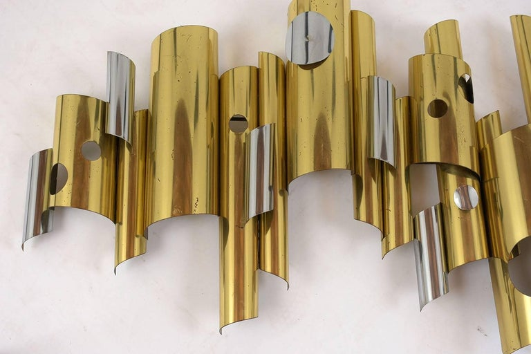 This 1960s Mid-Century Modern style wall sculpture is by C. Jere. The sculpture features brass and chrome cylinders in different sizes and lengths with cut out details. This sculpture is sturdy, stunning, and ready to be hung on any wall for years