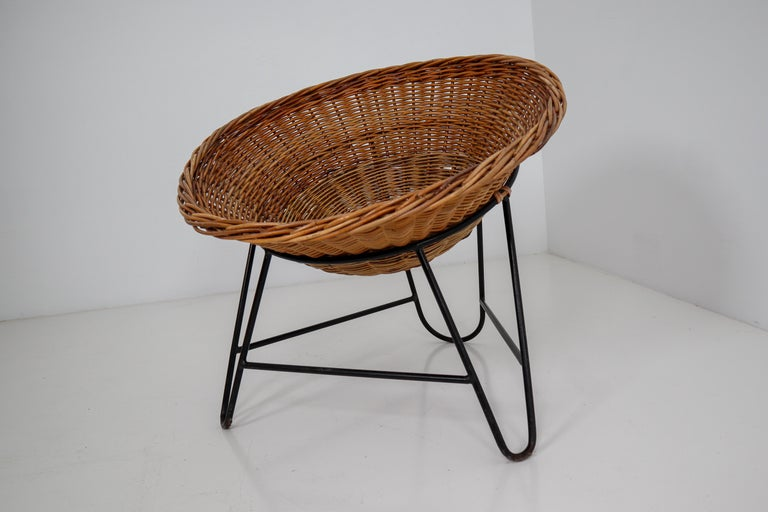 Large set wicker midcentury easy chairs designed and produced in Europe during the 1960s. The chairs are made from handwoven wicker for the seat that is formed into a basket. The frame is made of black lacquered steel. They are comfortable to sit in