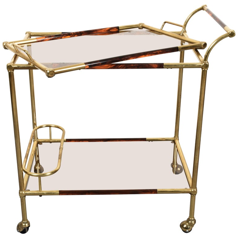 Elegant golden brass and Lucite tortoiseshell trolley. This item is attributed to Willy Rizzo and was produced in Italy during 1980s.  This item is very ductile as its top may be used as a wonderful service tray when needed. The bottom shelf has a