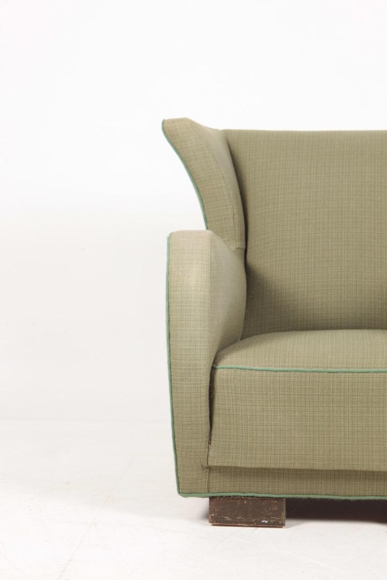 Wingback chair upholstered in fabric. Designed and made in Denmark.